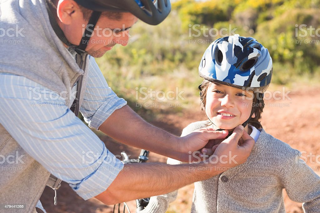 Father clipping on sons helmet stock photo