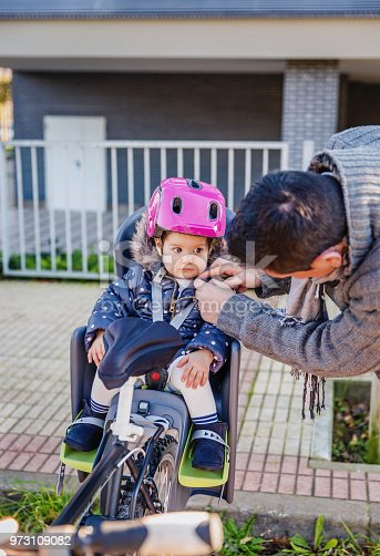 istock Father closing helmet to her daughter sitting in bike seat 973109082