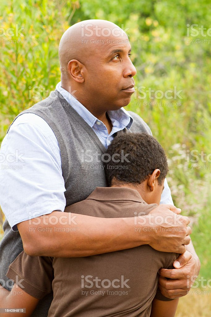 Father comforting his son stock photo