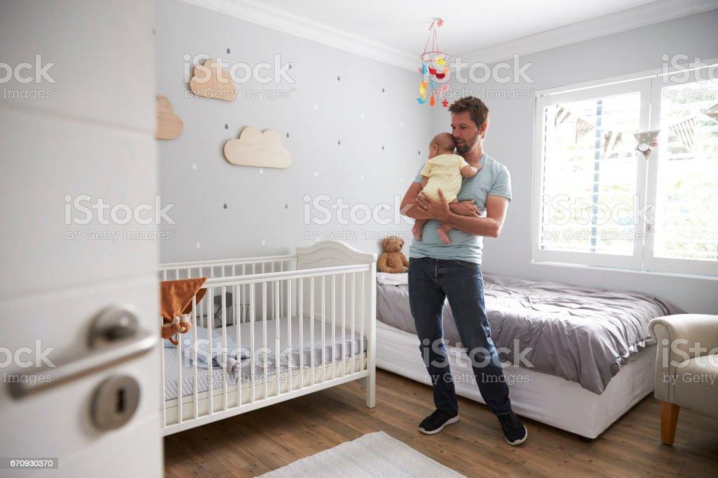 Father Comforting Newborn Baby Son In Nursery stock photo