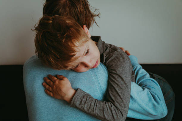 Father comforting sad child, parenting, sorrow stock photo
