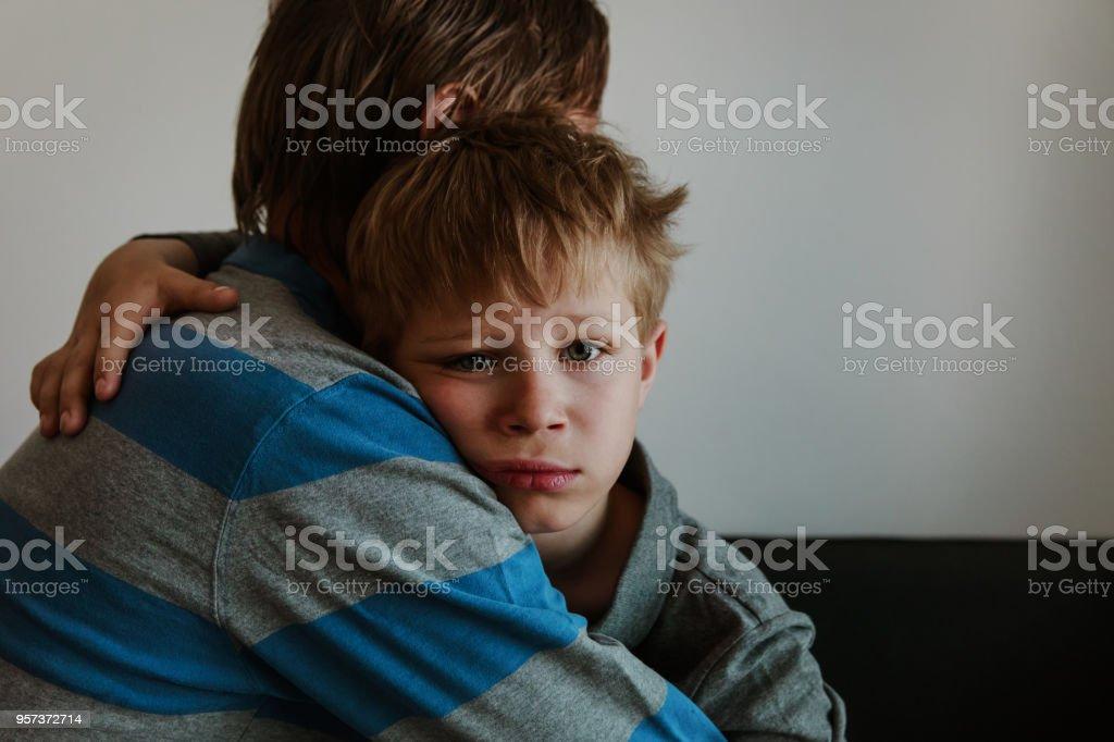 Father comforting sad child, parenting, sorrow stock photo