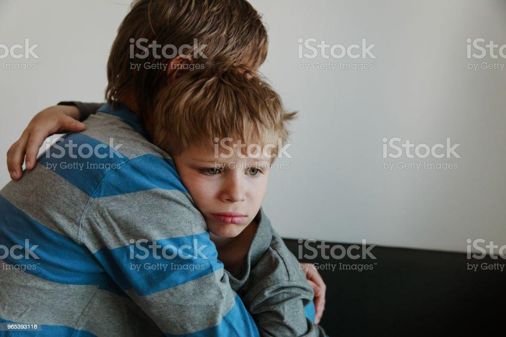 父親安慰哀傷的孩子, 養育, 哀傷 - 免版稅一起圖庫照片
