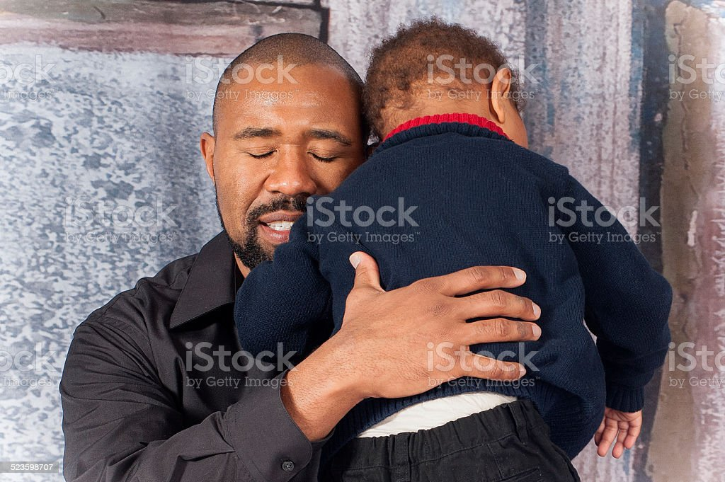 Father comforting son stock photo