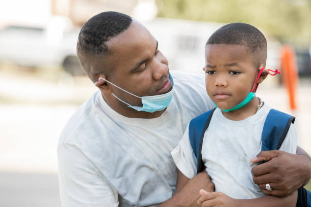 Father consoles anxious kindergartener while they wear masks as he's dropping him off for first day of school, stock photo