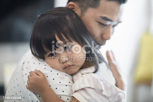 Father consoling cute daughter at home. Sad girl is looking away while shedding teardrops. They are at wearing casuals.