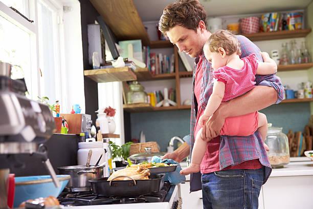 padre cocinar comida mientras sostiene hija en la cocina - padre que se queda en casa fotografías e imágenes de stock