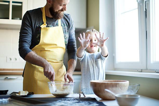 father cooking with his son - kids cooking stock photos and pictures