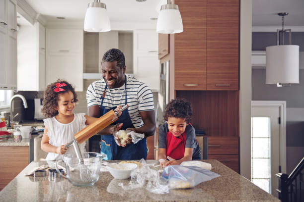 father cooking with kids - kids cooking stock photos and pictures