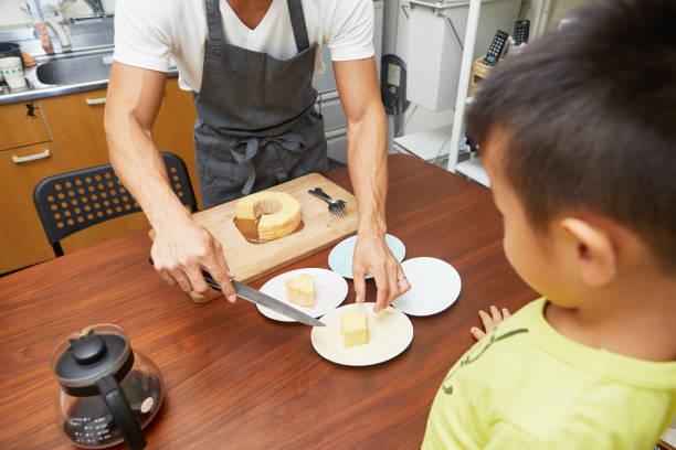 ein vater einen kuchen schneiden - hausmannskost stock-fotos und bilder