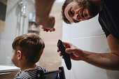 Father cutting son's hair at home during the 2020 pandemic lockdown. Covid-19 social distancing