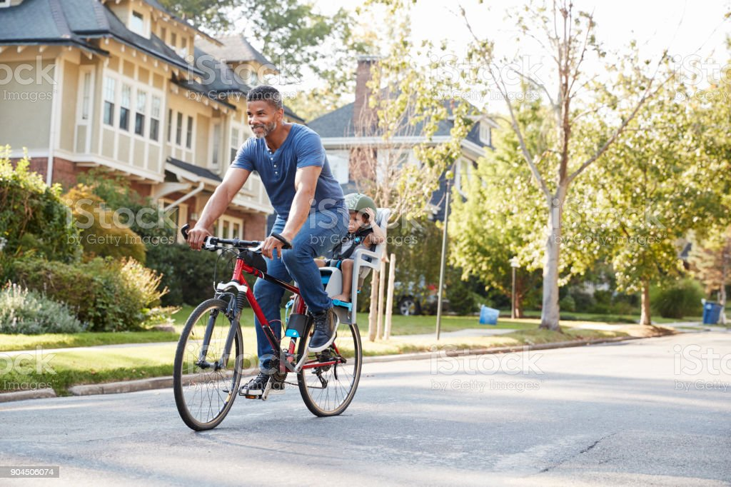 Father Cycling Along Street With Daughter In Child Seat stock photo
