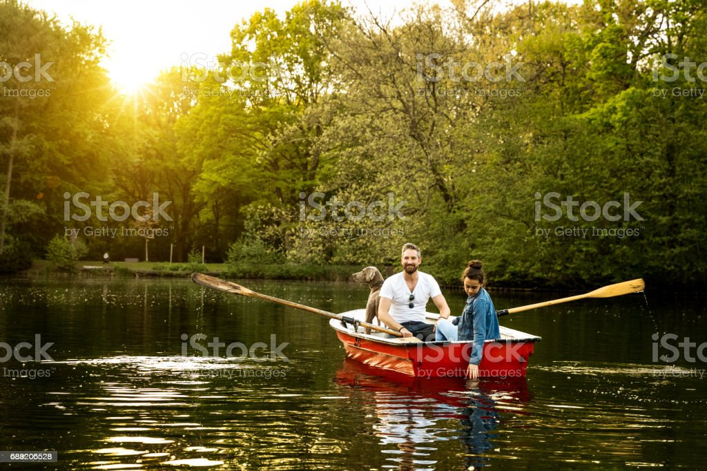 Father, daughter and dog in rowboat on lake stock photo