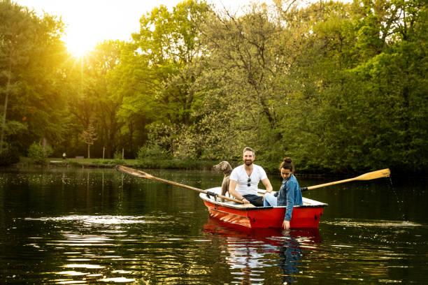 Père, fille et chien en barque sur le lac - Photo