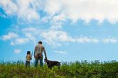 父と娘と草原で遊ぶ犬