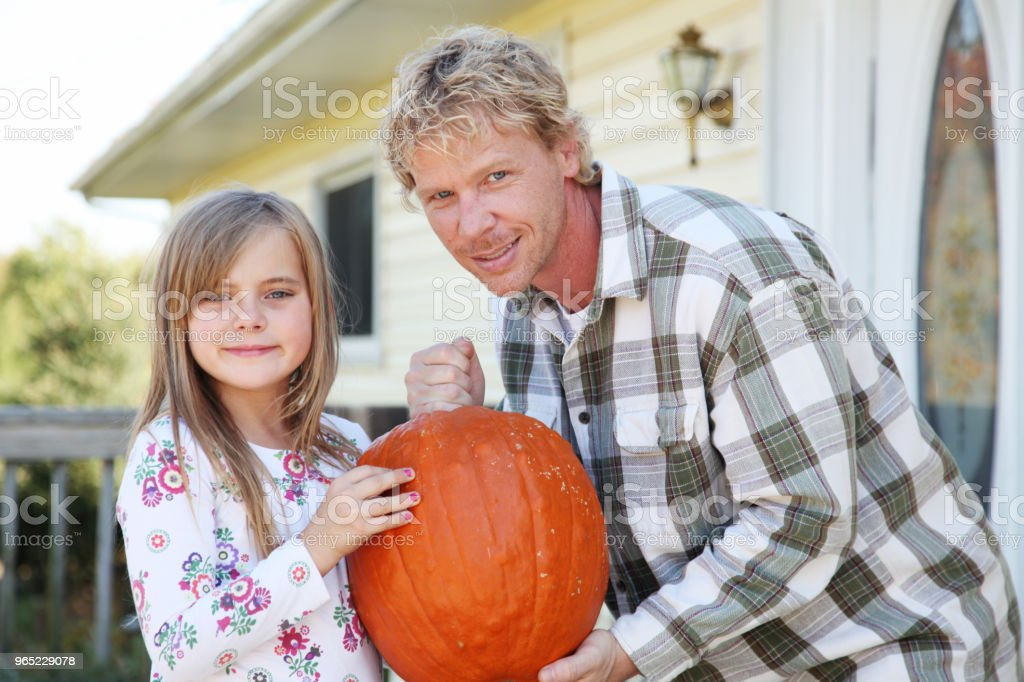 father daughter holding pumpkin zbiór zdjęć royalty-free