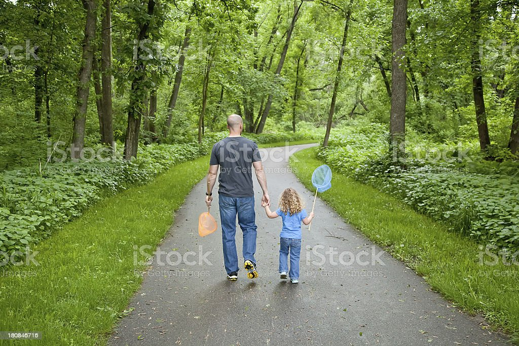 Father & Daughter Walking Through Park with Butterfly Nets royalty-free stock photo