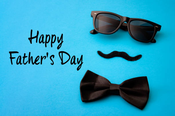 Father day and male hipster fashion concept with minimalist image of a pair of square sunglasses, black bowtie and a fake moustache on colorful blue background stock photo