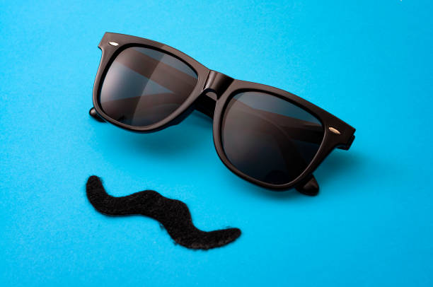 Father day and male hipster fashion concept with minimalist image of a pair of square sunglasses and a fake moustache on colorful blue background stock photo