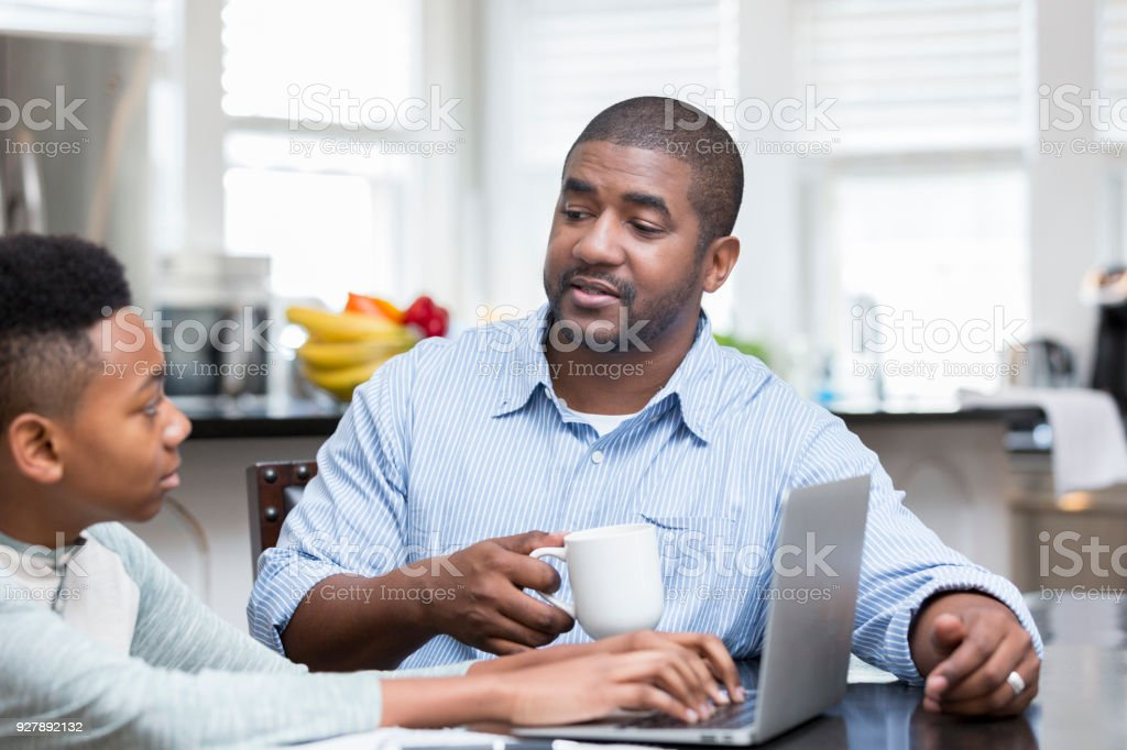 Father dictates life event for son's school project stock photo