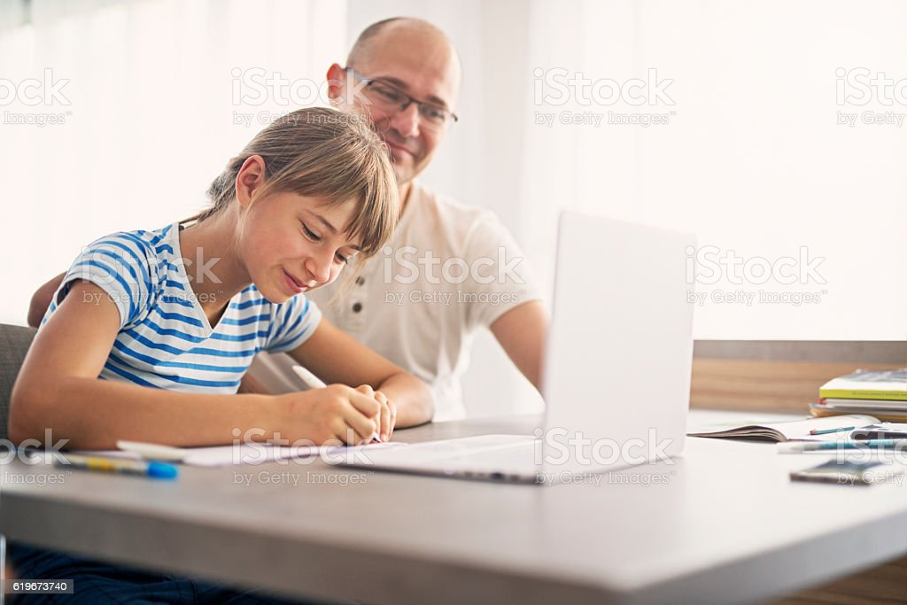 Father doing homework with his daughter stock photo