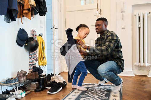 Father dressing up son in living room. Man is crouching while helping boy in wearing jacket. They are at home.