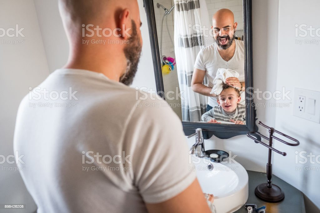 Father dries son's hair stock photo
