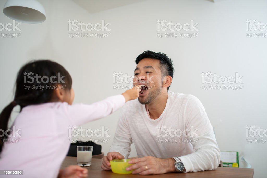 父娘で食べ物を家で食べる ストックフォト
