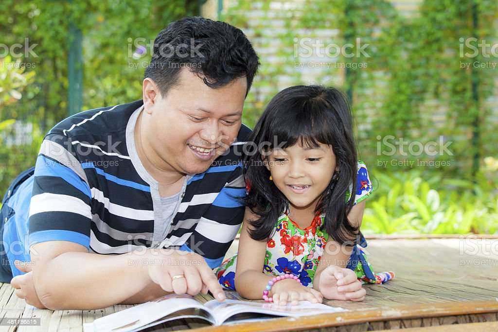 Father educate daughter with book in wood cottage outdoor stock photo