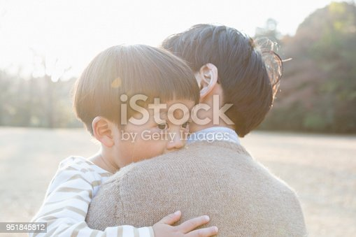 Japanese father consoling his son in the park.
