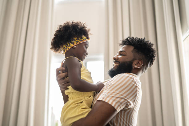 Father embracing daughter at home stock photo