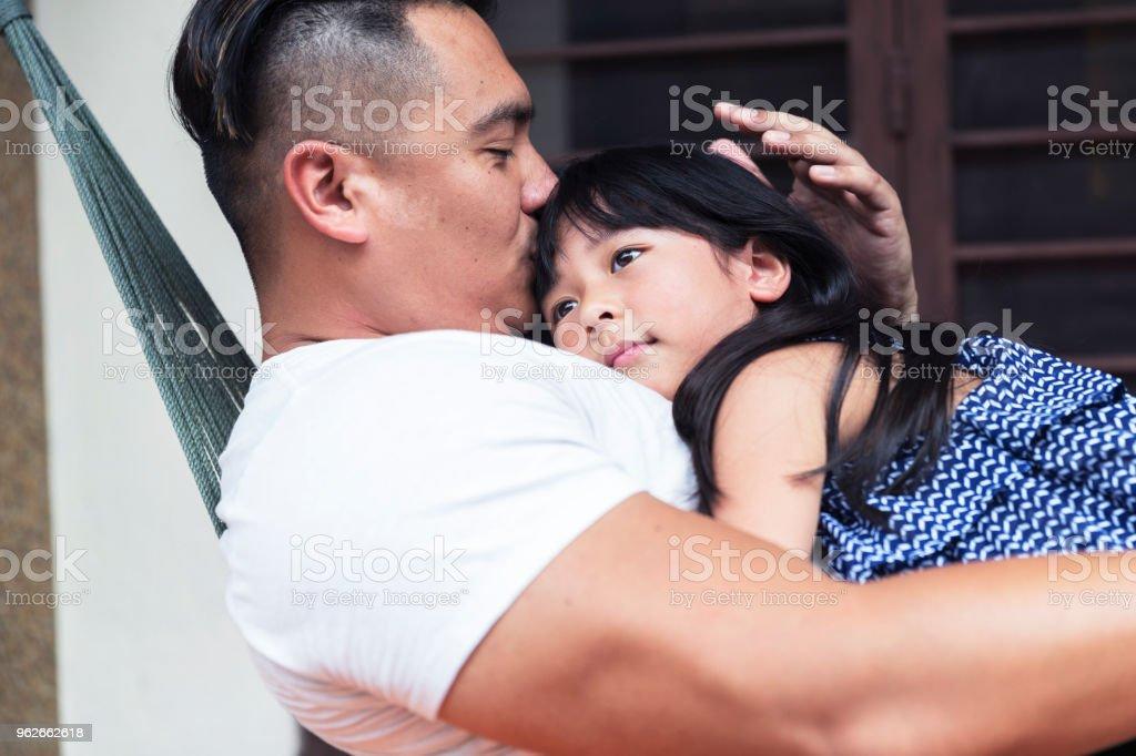 Le père embrassant sa fille et s'embrasser sur le front sur le hamac - Photo