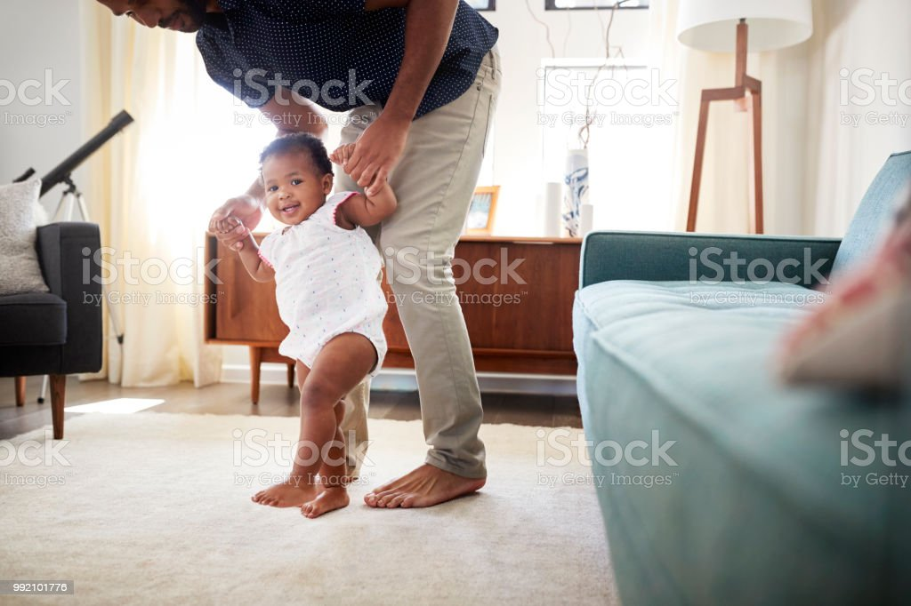 Father Encouraging Baby Daughter To Take First Steps At Home stock photo