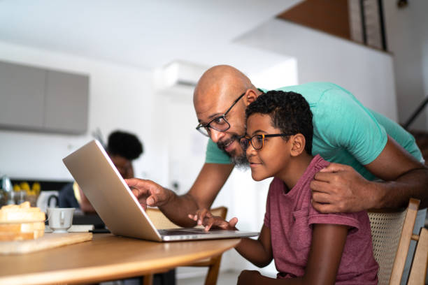 Father encouraging son on homeschooling or doing a video call/watching a movie stock photo