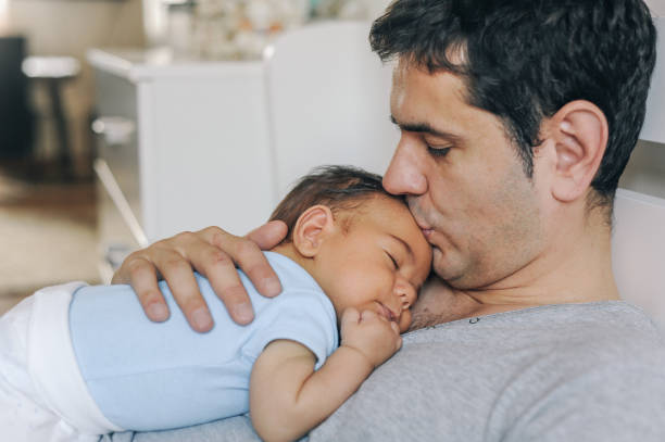 Vater genießt zu Hause mit seinem neugeborenen Kleinen Jungen – Foto