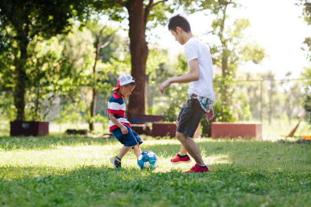 Father enjoying playing soccer with his kids stock photo