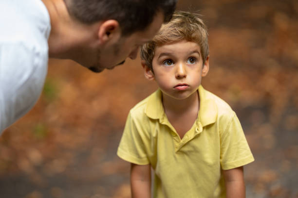 father explaining little boy son how to behave stock photo