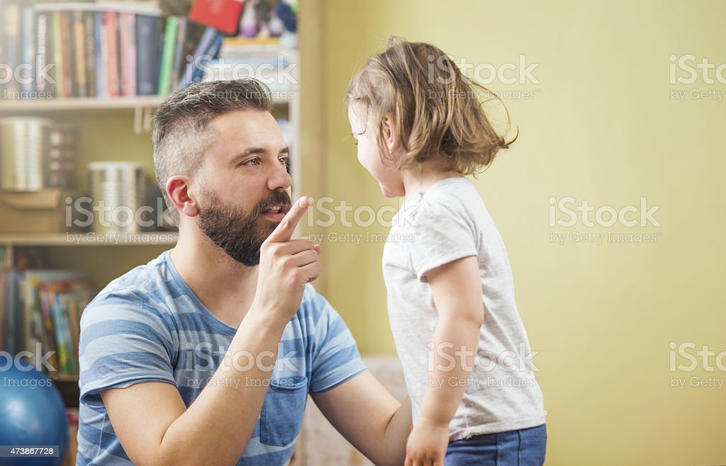 Father explaining something to his daughter stock photo