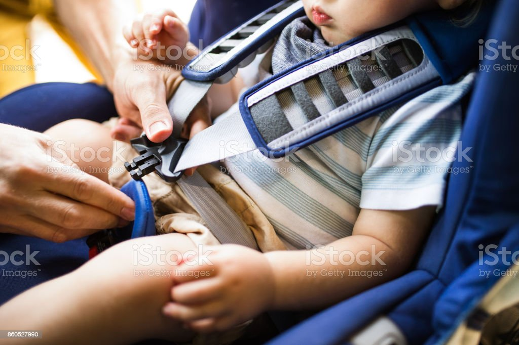 Father fastening seat belt for his son sitting in the car. stock photo