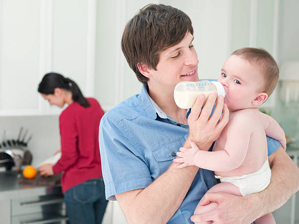 Father feeding baby bottle of milk stock photo