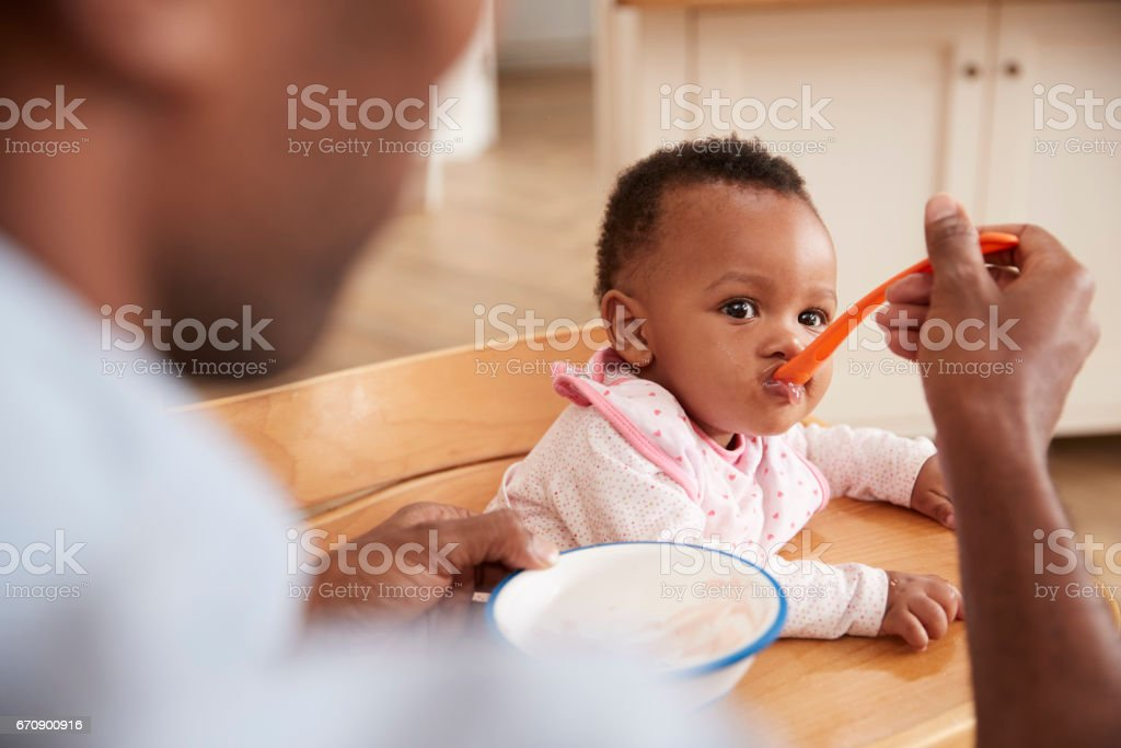 Father Feeding Baby Daughter In High Chair - foto de acervo