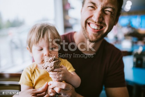 A dad feeds his one year old son a chocolate ice cream cone, the child enjoying sharing the sweet treat.  A depiction of a supportive and available father figure.