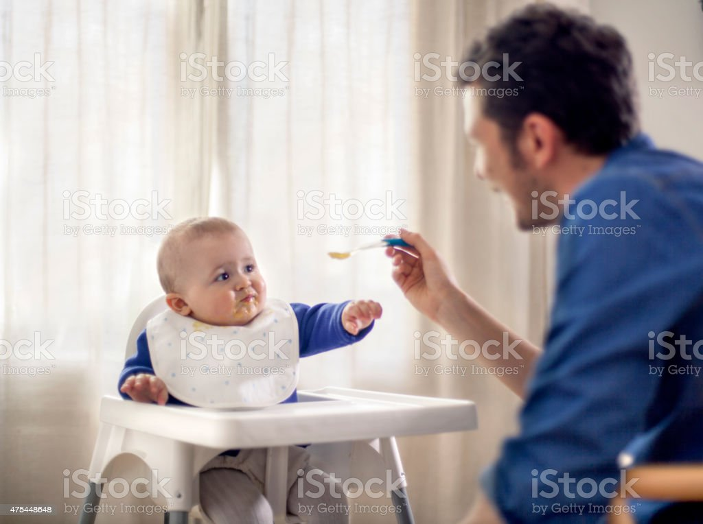 Father feeding baby in high chair stock photo