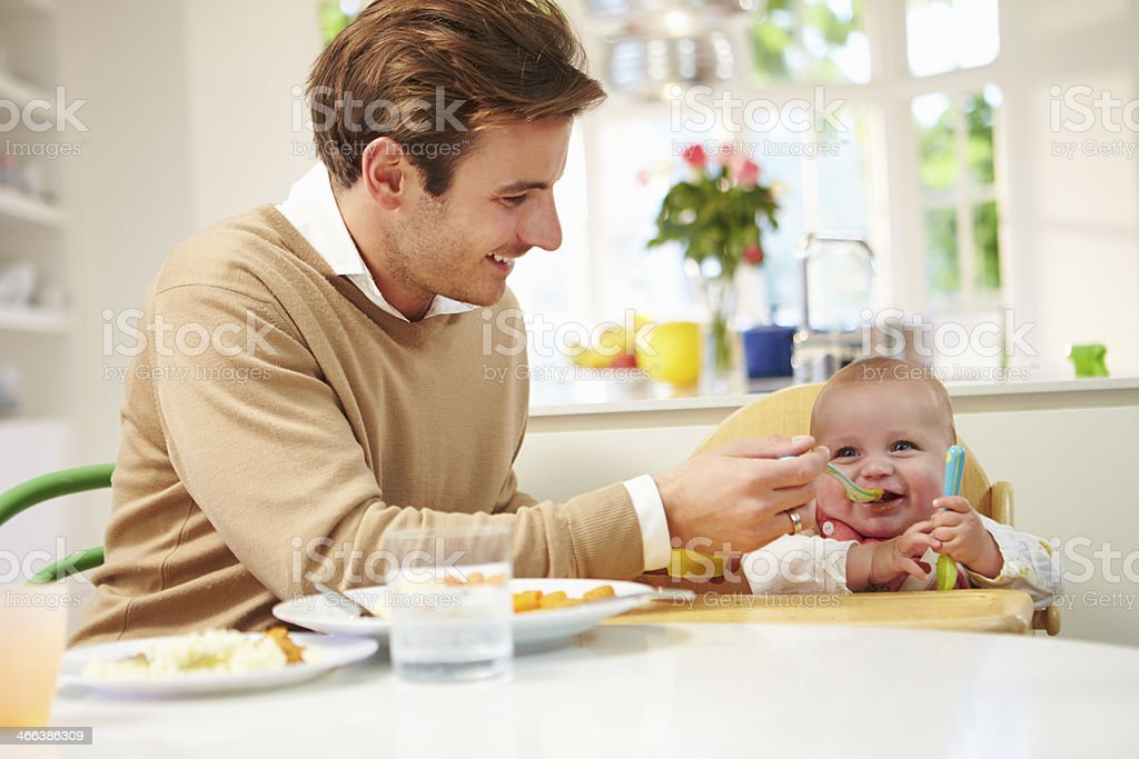 Father Feeding Baby Sitting In High Chair At Mealtime stock photo