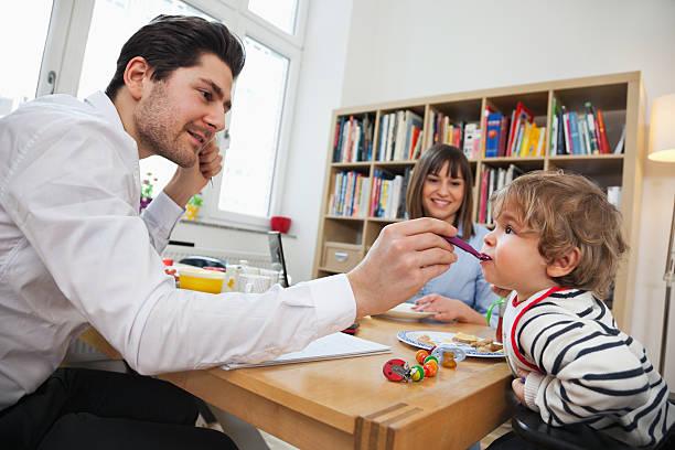 familie mit frühstück - kinderstuhl und tisch stock-fotos und bilder