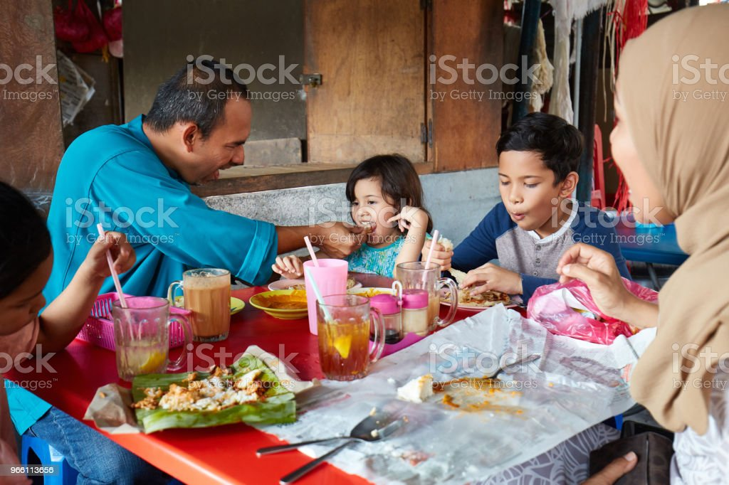 Father feeding daughter while sitting with family - Стоковые фото 10-11 лет роялти-фри