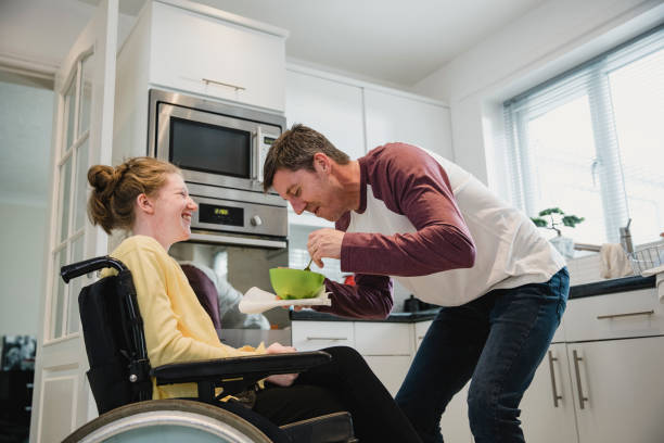 Father Feeding Disabled Daughter at Home Mature father is feeding his disabled teeenage daughter while she is sitting in a wheelchair in the kitchen of their home. amyotrophic lateral sclerosis stock pictures, royalty-free photos & images