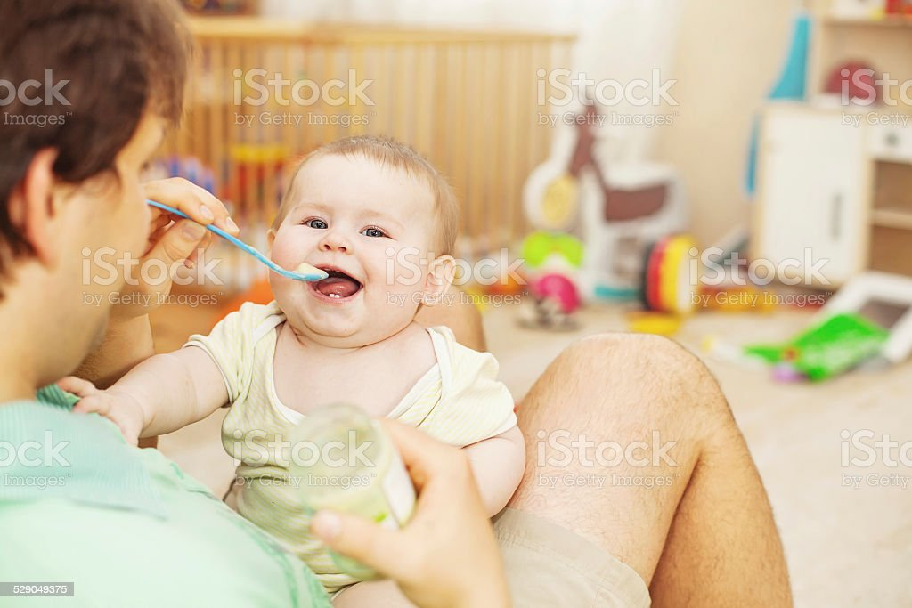 father feeding his cheerful baby stock photo
