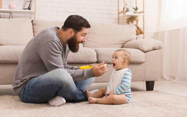 vater füttert seinen niedlichen baby-sohn zu hause - füttern stock-fotos und bilder