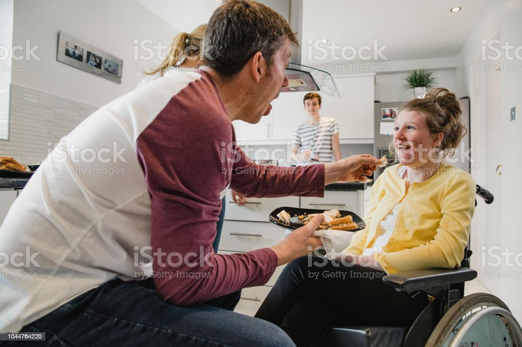 Father Feeding his Disabled Daughter Lunch stock photo